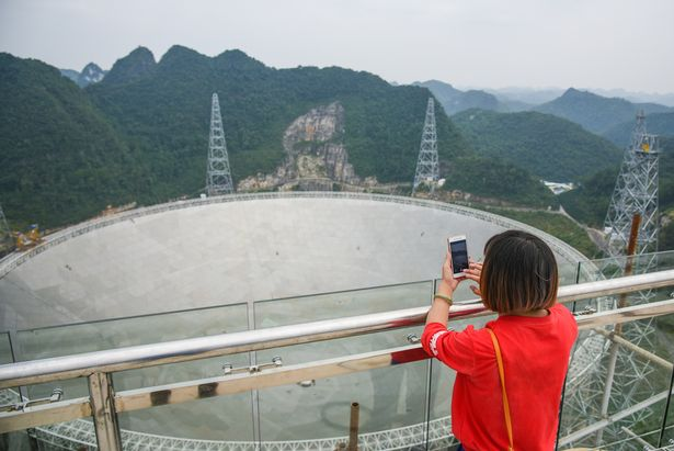 A woman takes photos of the FAST telescope in Pingtang County, southwest China's Guizhou Province